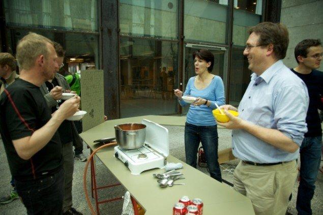 Kunstneren Nis Rømer (til venstre) serverer suppe ved ferniseringen af Imaginistisk Velfærdsarbejde. Pressefoto.