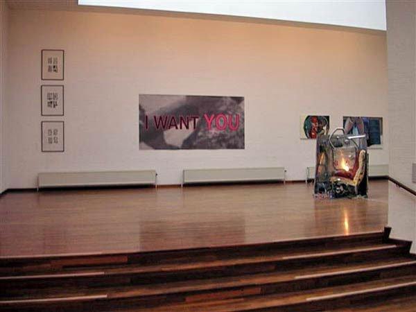 Nikolaj Bendix Skyum Larsen: Blind date, 2007. Papir på print, 301x151 cm. Til højre anes Jesper Fabricius's  tredelte værk. I forgrunden Franz Beckerlees installationsskulptur My Travel, 2005. Foto: Lars Skovfoged.