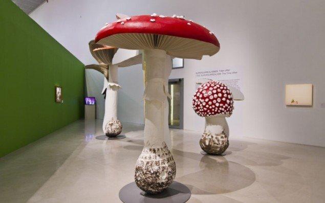 Udstillingsview med Casten Höllers Giant Triple Mushroom, 2012 i forgrunden. I baggrunden skimtes Nathalie Djurbergs claymation-video Florentin, 2004. (Foto: Terje Östling)