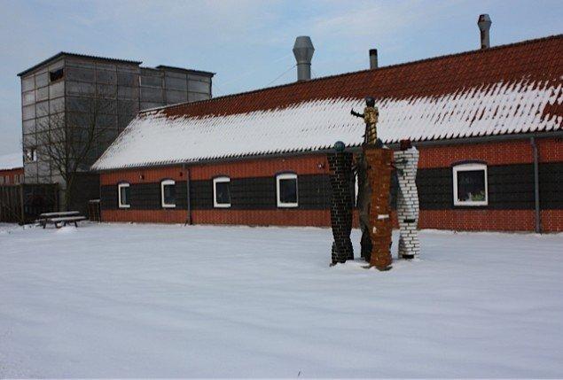 Tommerup Keramisk Værksted set fra forsiden med skulptur af Bjørn Nørgaard i forgrunden og bygning med højovn i baggrunden. Foto: Trine Rytter Andersen