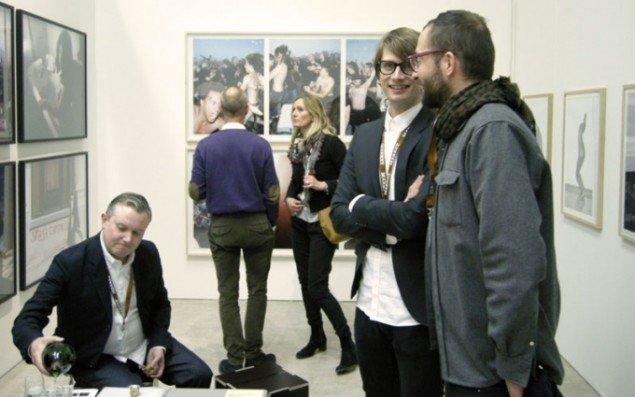 Mikkel Grønnebæk (siddende) og Jesper Elg i deres V1 stand. V1 havde en større præsentation af Jacob Holdts fotografier med på messen.