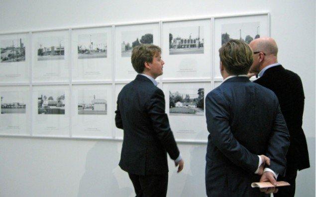 Gallerist Nicolai Wallner (til venstre) foran fotoværker (Occupied Plots) af Joakim Koester.