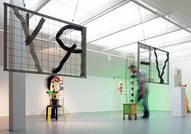 Miguel Vega Olivares i ovenlyssalen i SAK Kunstbygning, set gennem værket Recovery, blandede materialer. Foto: Jerry Jakobsfeld