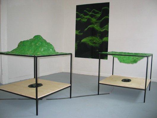 Forgrund: Twilight, 2006. Glasfiber, stål, træ, højtaler, musik komponeret af Jakob Myrhøj. Baggrund: Hills in Haifa, 2006. Lambdafoto, 100x150 cm. Fra udstillingen Grænseland. Foto: Lene Desmentik
