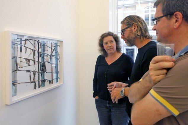 Gallerist Frank Rosenmejer viser detaljerne i Andreas Johanssons unikke kollager som alle er håndsudskårne med skalpel. Foto Carsten Nordholt