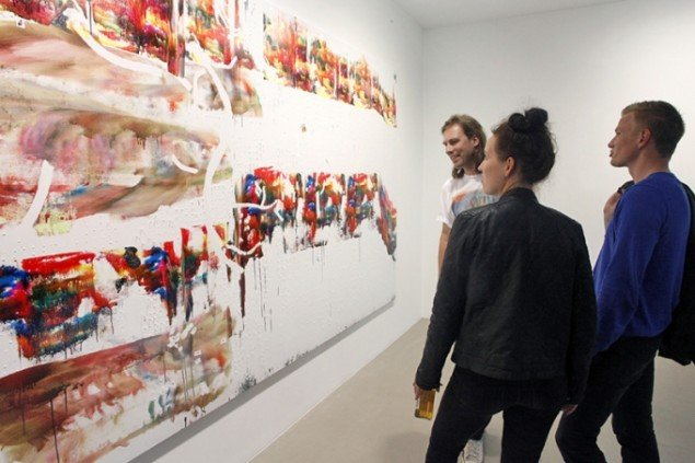 Gallerist Christian Andersen betragter værkets tørringsproces sammen med et par besøgende. Foto Carsten Nordholt