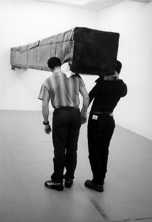 Santiago Sierra  Objekt 600 x 57 x 52 cm, konstrueret, skal holdes horisontalt imod væggen  Aktion i Galerie Peter Kilchmann. Zürich, Schweiz. April 2001, Træ, tagpap og andre materialer,, 600 x 57 x 52 cm. © VG Bild-Kunst, Bonn 2013