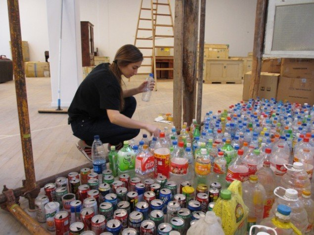 En assistent placerer tomme emballager i skelettet til Songs mors hus. Foto: Kirstine Bruun