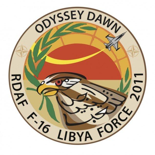 Det officelle missionsmærke til den danske indsats i Libyen-krigen 2011. Vævet stofmærke, ø 10 cm. Mærket viser en FredsFalk, UN's fredsgren og teksten Fred for det Libyske folk på arabisk. Samarbejde med Ali Fahrek Muhamad
