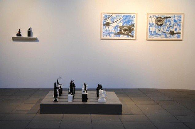 Udstillingsview, Mostly Black and White, Kunstpakhuset 2014. Bjarne W. Troelstrup: Totem. Skulpturer, varierende størrelser, bemalet træ (2012-13) og Troels Wörsel: To litografier, papirformat 54 x 76 cm. (2012). Foto: Bente Jensen