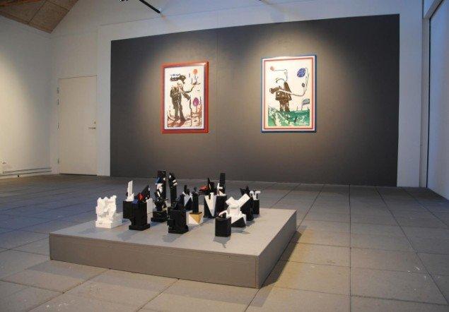 Udstillingsview, Mostly Black and White, Kunstpakhuset 2014. Bjarne W. Troelstrup: Totem, skulpturer, varierende str., 2012-13 og John Kørner: litografier fra serien Gallery Fruits, 2007. Foto: Bente Jensen
