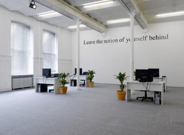 Mantraet, der fungerer som underbevidsthedens barrikade står højt og klart på bagvæggen i det kølige kontorlandskab. Foto: Anders Sune Berg
