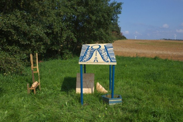 Del af Sara Villemoses rumlige komposition på en stor græsmark. Den består af 5 skulpturer, hvor hver skulptur består af delelementer. Man kan danne sig et overblik over helheden ved at bevæge sig rundt på marken. Foto: Skulpturlandsby Selde