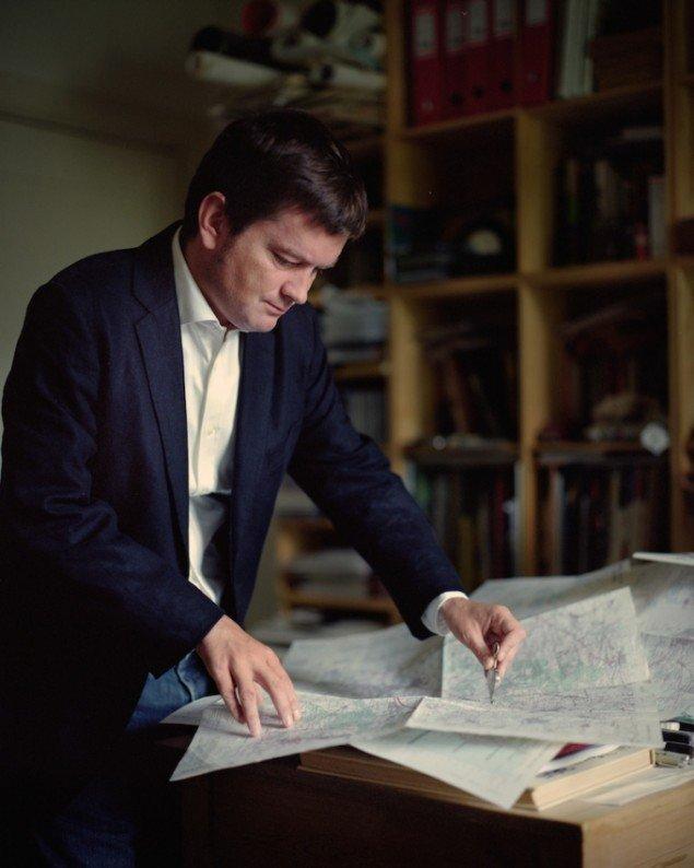 32. A man running a milometer across a map, 2006. Fra den fotografiske serie 59 Illustrations, (2006 -)