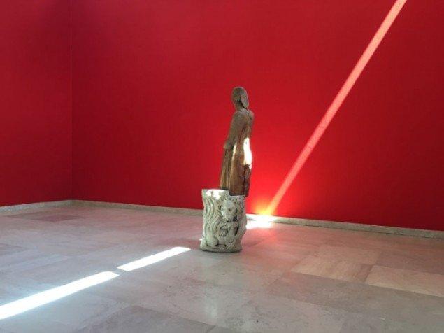 Installationsview med vægge i rød silke og sammensat objekt af træmadonna og stykke af romersk sarkofag, Mothertongue, Den Danske Pavillon, Venedig Biennalen 2015. (Foto: Jan Falk Borup)