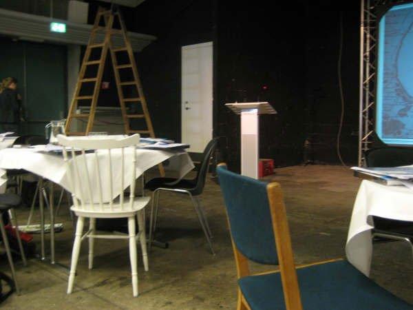 Nørrebrohallens talerstol og i forgrunden stole fra Fighters+Lovers. Foto: Lise Bøgh Sørensen