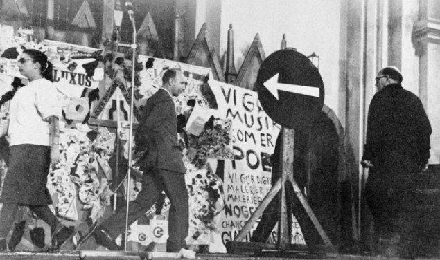 Blandt andre Eric Andersen (bag skiltet) og musiker Emmett Williams opfører George Brechts One Direction, 1961. (arkivfoto)
