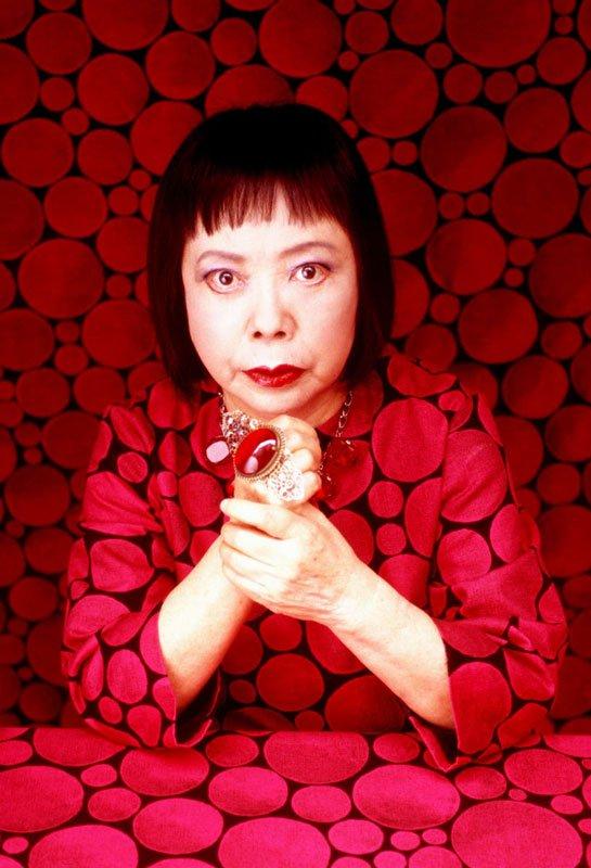 Kusama omgivet af mønsteret Stars, som hun designede til et samarbejde med det japanske designkollektiv graf, 2002