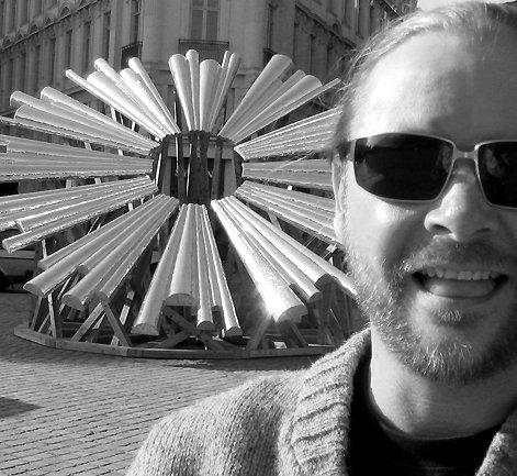 Benny Dröscher med skulpturværket Jeg er så træt af at være ateist i baggrunden. Foto: Sonnich Morgenstern