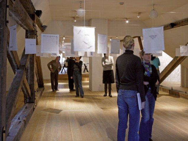 Publikum lytter til lydnoterne og læser de håndbroderede tekster.  noter til ensomhed Kvindemuseet, 2008. Foto: Gert Skærlund Andersen