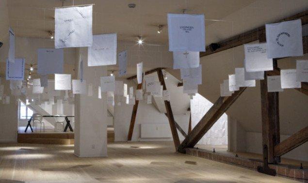 Enkelthængende, bevægelige, nye damelommetørklæder med håndbroderede tekster og i baggrunden sybordet til publikum.  noter til ensomhed Kvindemuseet, 2008. Foto: Gert Skærlund Andersen