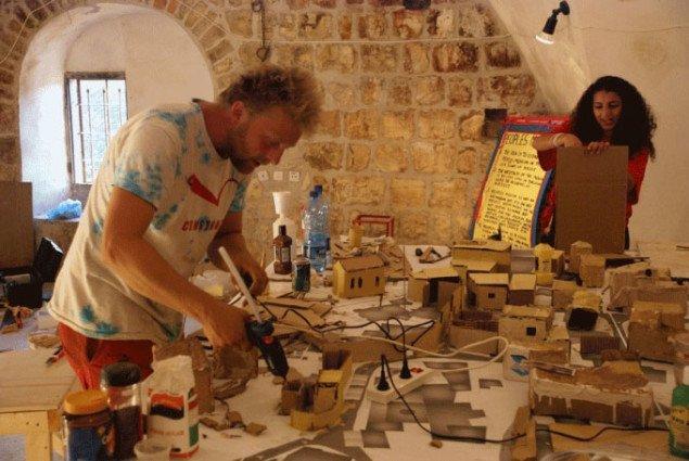 Pelle fra kunstnergruppen Parfyme og Yaliano som studerer på den Latinske Skole i Birzeit arbejder på minimodellen af byen. Foto: YNKB