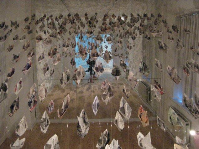 En bølge af papirsbåde fylder rummet og fordobles i det itubrudre spejl. Gerda Thune Andersen, We are All in the Same Boat, 2009, Foto: Kasper Lie.
