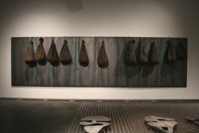 Jannis Kounellis, Uden titel, 2003 (200 x 720 x 43 cm), jernplader, kroge, 11 sække med kul. Foto Bente Jensen