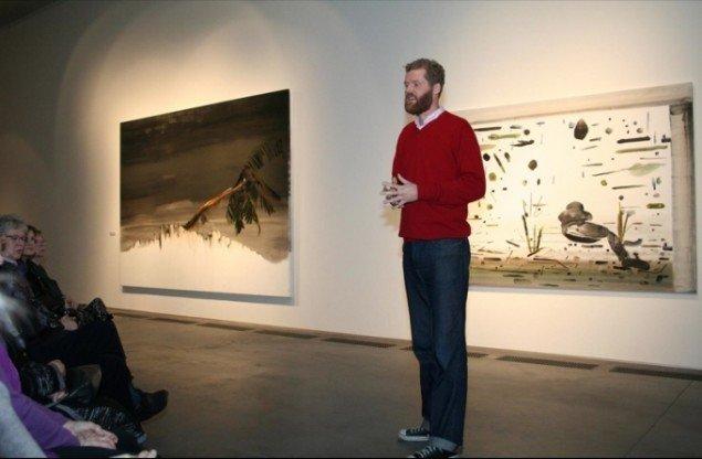 John Kørner ved artist talk. I baggrunden ses Afghanistan-billederne Christian (venstre) og Sebastian (højre). Foto: Lasse Oxbøll