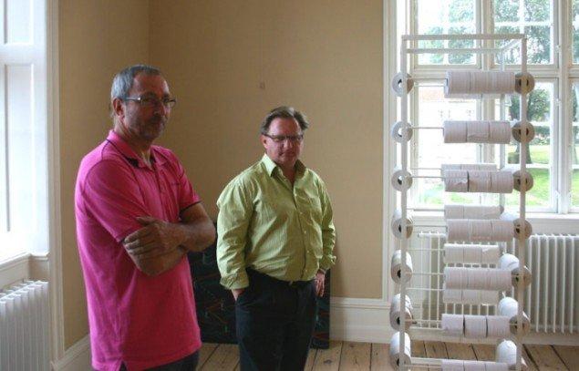 Claus Bohne og Bernt Petersen i gang med at sætte udstillingen op. Værket til højre er Jørgen Carlo Larsen: 'Normalisering'. Foto: Kristian Handberg.