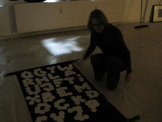 Henriette Heise er ved at gøre værket Night writing klar til ophængning i det meget mørke bagerste lokale. (Foto: Mia Keinicke)