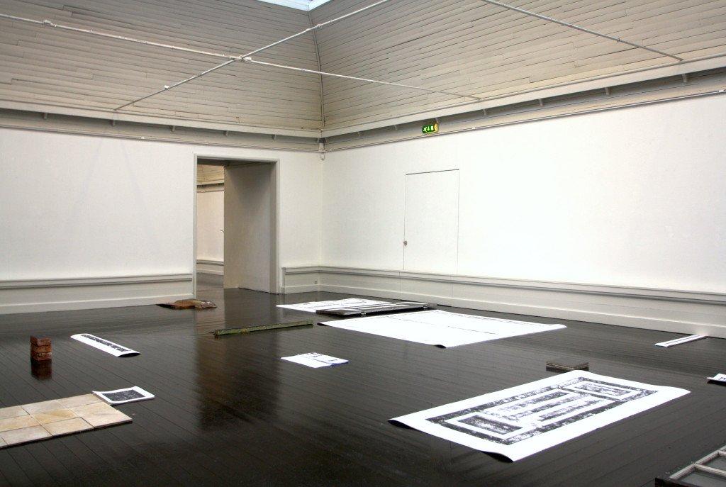 Vinduesrammer, en dør, mursten og papirark med aftryk fra disse er placeret i et system uden hierarki i Anni's og Mette Winckelmanns arkitektoniske installation Hjælpens sten, 2016. Foto: Anne Thomasen