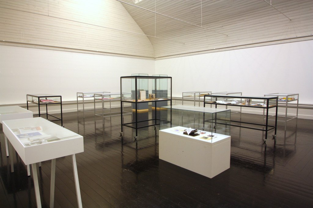 Kunstnerbøgerne, der danner inspiration til de udstillende kunstneres rumlige værker, er præsenteret i klassiske glasmontre og bliver udstillingens historiske og internationale arkiv. Foto: Anne Thomasen