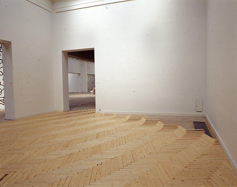Lind har ovenpå det eksisterende gulv monteret et lag af parketstave, der indledt i et sildebensmønster, strækkes ud og lægges i et nøje beregnet forskydningsforhold. Temporary Spaces, 2003. Installation, Charlottenborg. Foto: Karin Lind