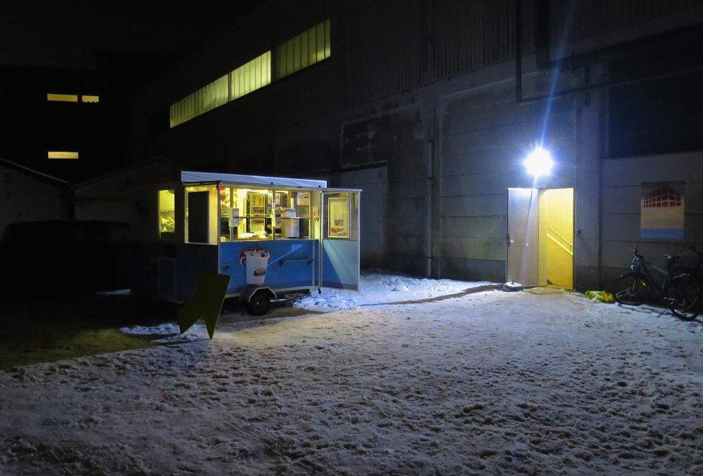 Hejsningen af pølsevognen lykkedes ikke. Publikum blev dog ikke snydt for de varme pølser. Vognen slog sig ned i sneen udenfor. Foto: Kulturdivisionen Slagteriet Holstebro