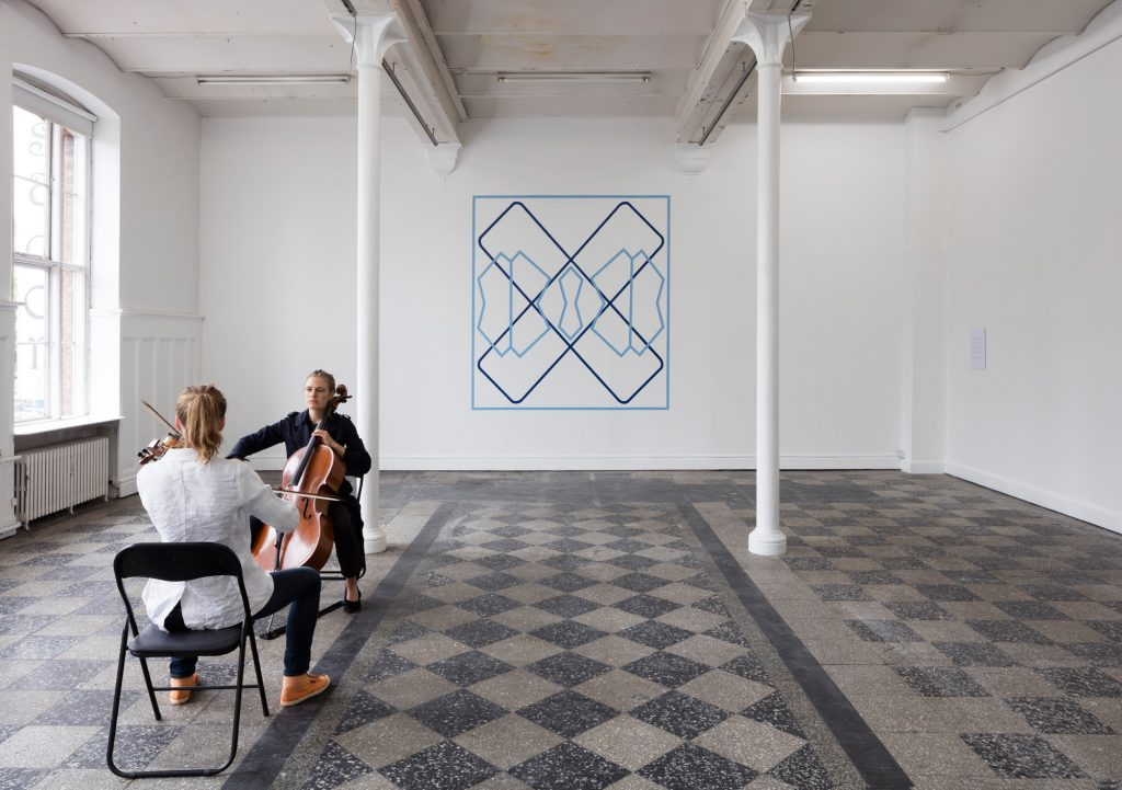 I anledning af åbningen af rum mål lyd tid præsenterede Ursula Nistrup en ny stedsspecifik performance, skabt i samarbejde med Cæcilie Trier (cello) og Maria Diekmann (violin). Med afsæt i kunstnerens bidrag til udstillingen opførte de to komponister en ny musisk komposition, hvor de hver 'spillede' et af de to blå mønstrer, der kan ses på væggen bag dem. Foto: Anders Sune Berg